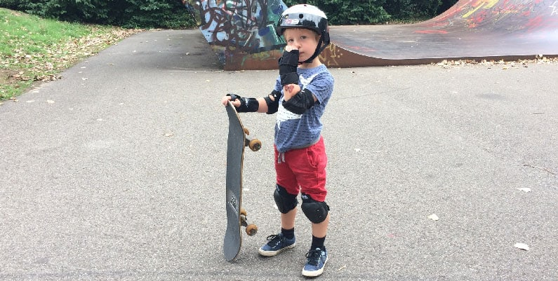Boy wearing full protective gear and a skateboard.jpg